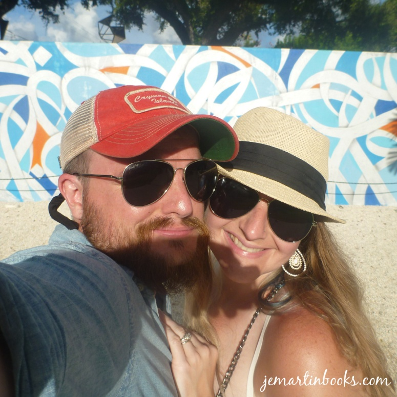 Image of a smiling man and woman in sunglasses and hats standing in front of a graffiti-covered wall at Wynwood Walls in Miami